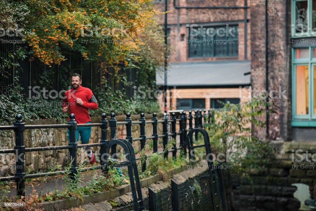 Single Man Running At Dusk Stock Photo - Download Image Now