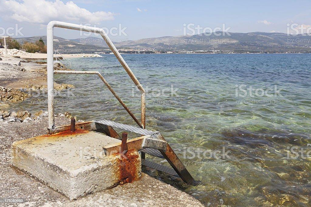 single metal staircase at turquoise mediterranean beach Trogir Croatia royalty-free stock photo