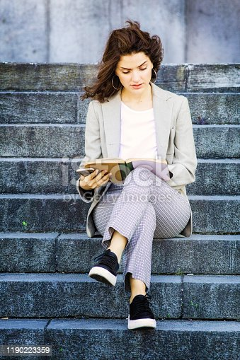 Single millennial female student reading a book sitting on stone steps full length. She holds her phone as well.