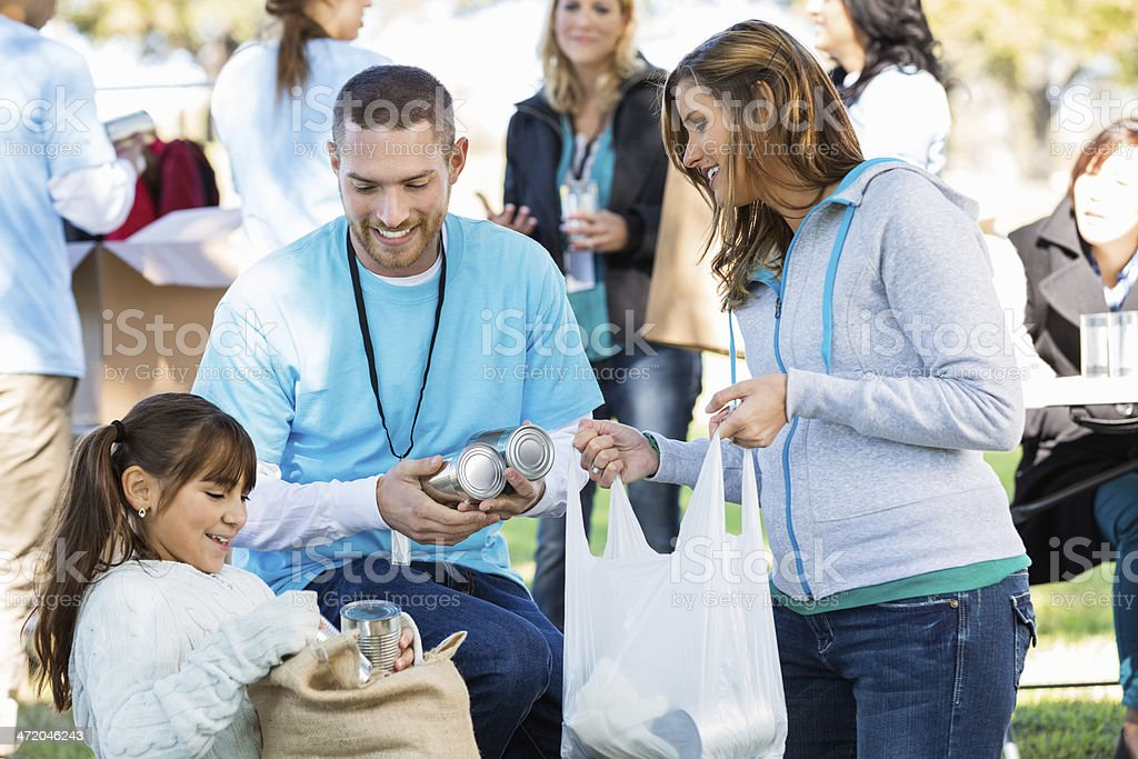Single mom and daughter accepting food donations from volunteer stock photo