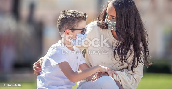 Single mom is looking worried at her son in sunglasses outside, both wearing face masks.