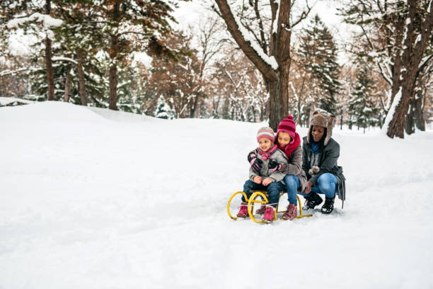 Single mom playing with kids at snow stock photo