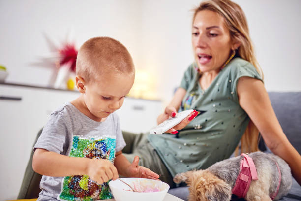 Single mom with TV remote, kid and dog in the living room. stock photo