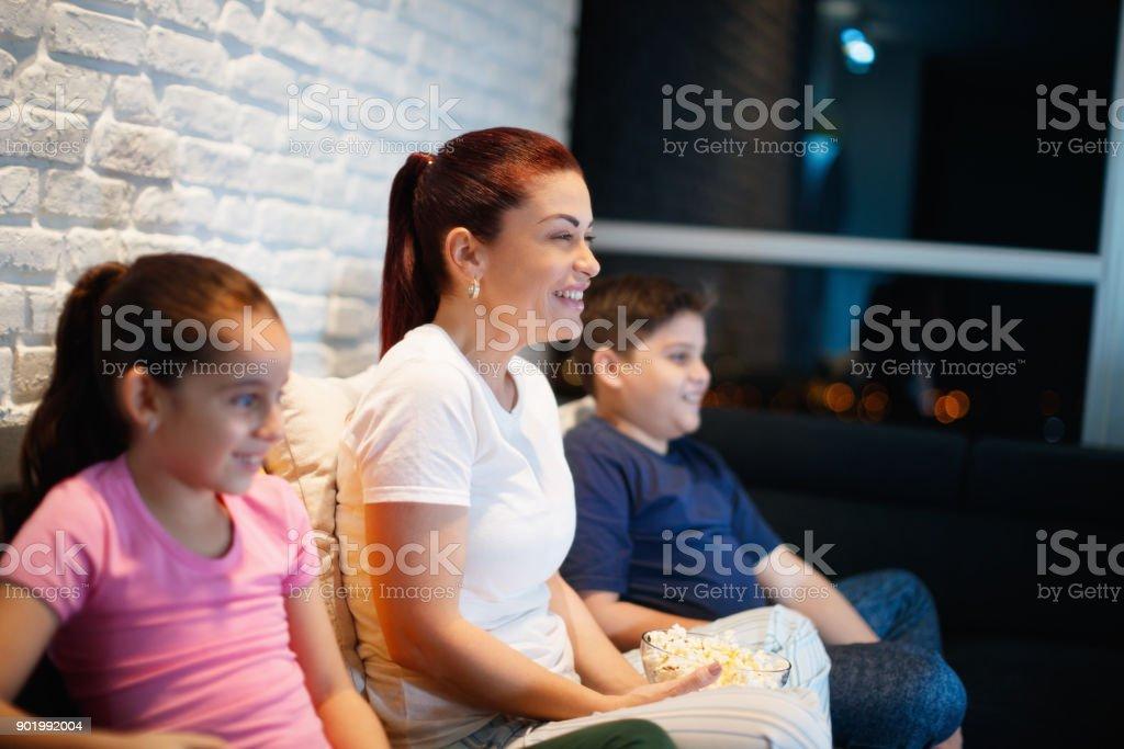 m re c libataire et les enfants regardent la t l vision dans la nuit photos et plus d 39 images. Black Bedroom Furniture Sets. Home Design Ideas