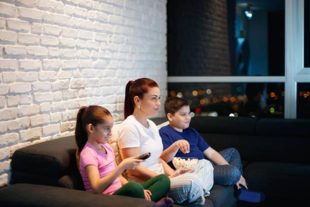 alleinerziehende mutter und kinder vor dem fernseher in der nacht - mädchen night snacks stock-fotos und bilder