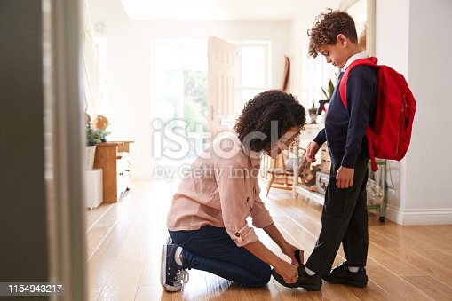 Single Mother At Home Getting Son Wearing Uniform Ready For First Day Of School