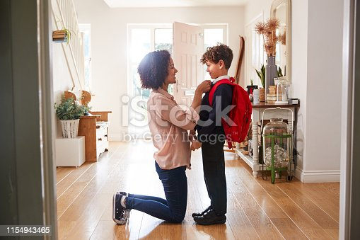 istock Single Mother At Home Getting Son Wearing Uniform Ready For First Day Of School 1154943465