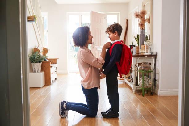ensamstående mamma hemma få son klädd uniform redo för första dagen i skolan - förälder bildbanksfoton och bilder