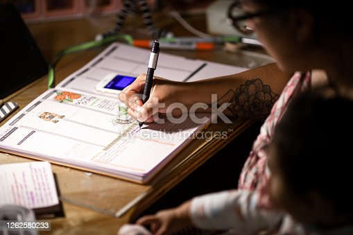 Single mother makes a weekly schedule at her desk and is holding her baby daughter. Shot inside of a home in Washington USA.