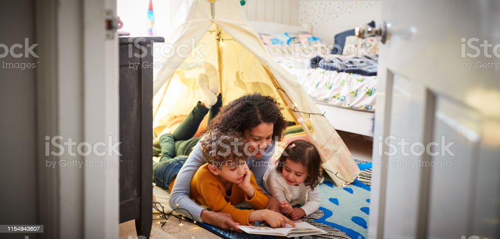 Single Mother Reading With Son And Daughter In Den In Bedroom At Home - Foto stock royalty-free di 2-3 anni