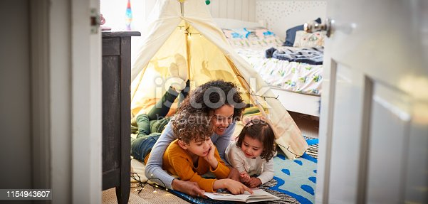 istock Single Mother Reading With Son And Daughter In Den In Bedroom At Home 1154943607
