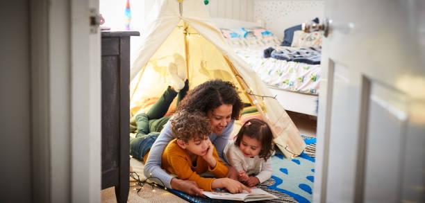 madre single che legge con figlio e figlia in tana in camera da letto a casa - family foto e immagini stock