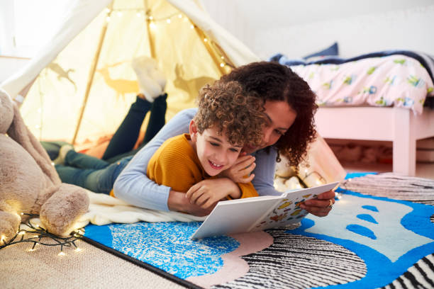 Single Mother Reading With Son In Den In Bedroom At Home – Foto