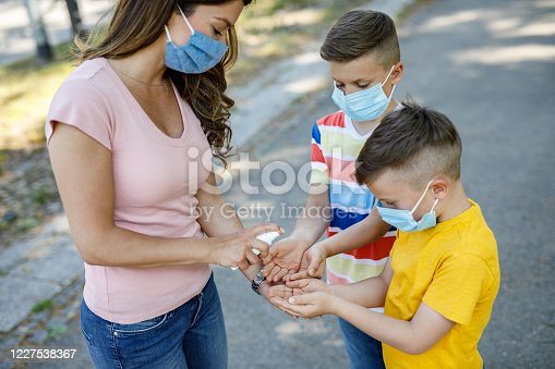 Single mother spraying hand sanitizer to her little children hands, everyone wearing protective masks