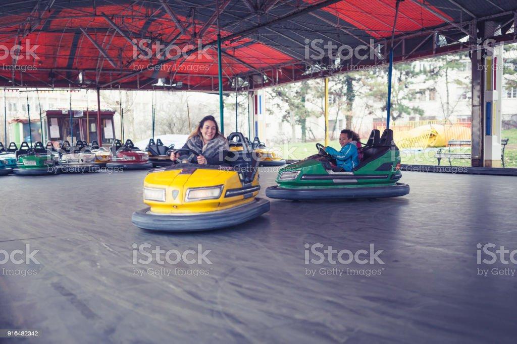 Alleinerziehende Mutter mit Kindern, fahren Autoscooter im Vergnügungspark – Foto