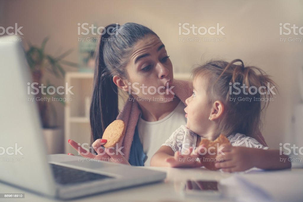 Single mother with her daughter at home having breakfast and making funny face. Close up. stock photo