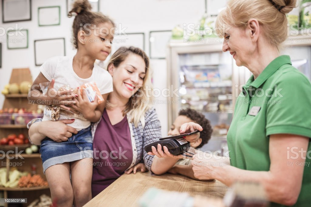 Single mother with her mixed-race kids is making a contactless payment at the store stock photo