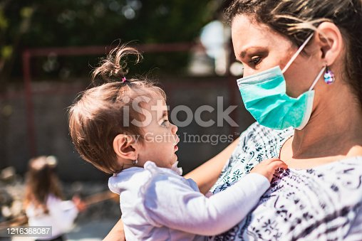 Single mother with pollution mask holding a baby girl. They are outside.