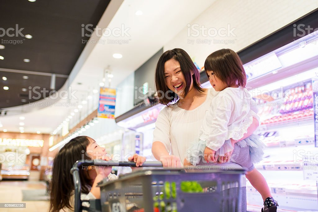 Single mother with two kids shopping in a supermarket stock photo