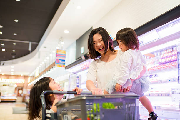 single mother with two kids shopping in a supermarket - スーパーマーケット 日本 ストックフォトと画像