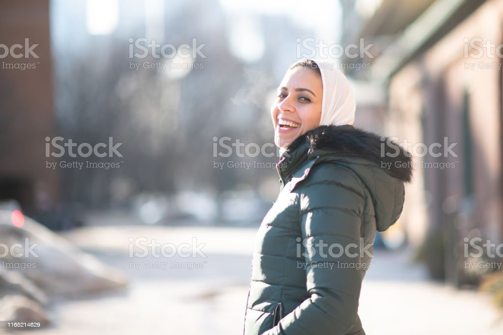 Single Muslim Woman A beautiful Muslim woman smiles in this portrait taken outside during the winter. She is bundled up to keep warm and has her hands in her pockets. She is joyous. Adult Stock Photo