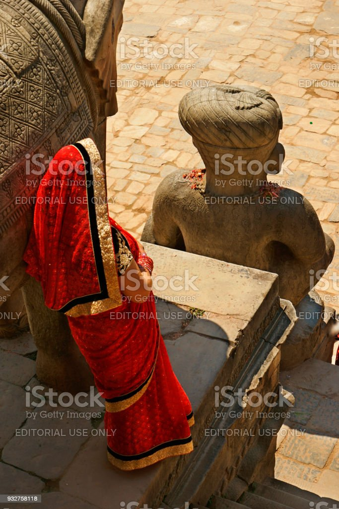 single nepalese women in red Sari leaning against temple statue stock photo