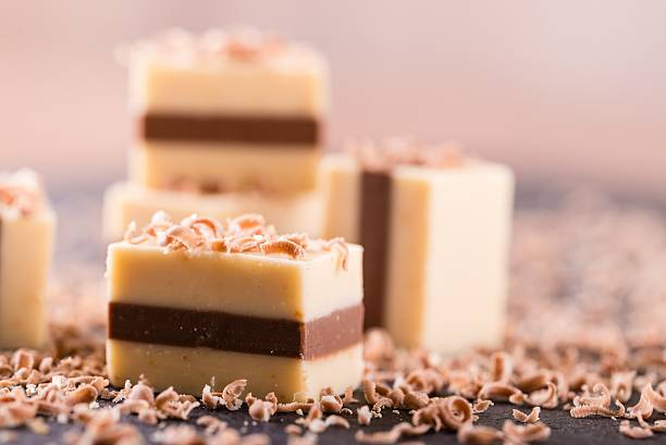 Single nougat cube on slate plate in front of others stock photo