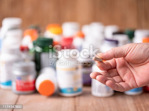 A single nutritional health supplement capsule being held in a hand before consuming it, with many colorful food supplement and vitamin bottles out of focus in the background on a wooden table. Selective focus with the focus being on the capsule in the hand. Lifestyle, diet and healthy eating concept image relating to the vast array of food supplements and vitamins available for sale and the choices people make in relation to eating a balanced fresh food diet.