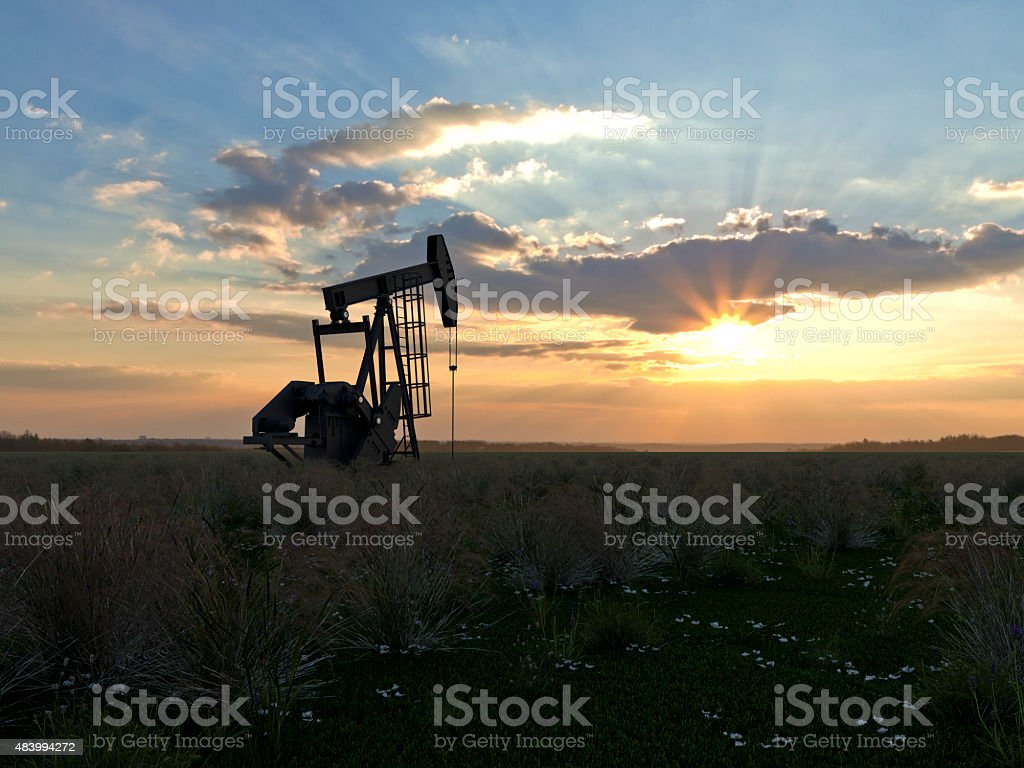 single oil rig in the sunset on a field stock photo