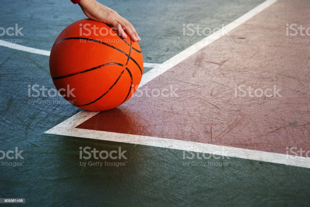 single orange basketball with woman player hand on green red sport gymnasium floor background stock photo