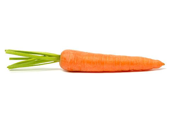 Single orange carrot with stalk on a white surface stock photo