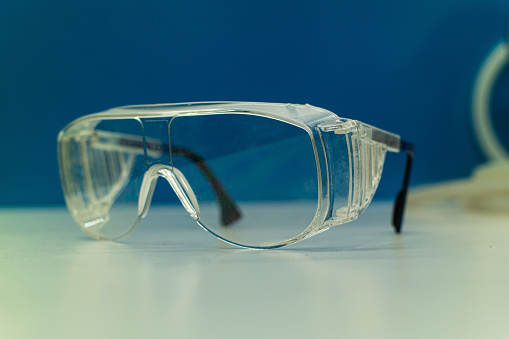 Single pair of clear protection goggles on a table inside a science laboratory isolated against blue background shallow depth of field 2020