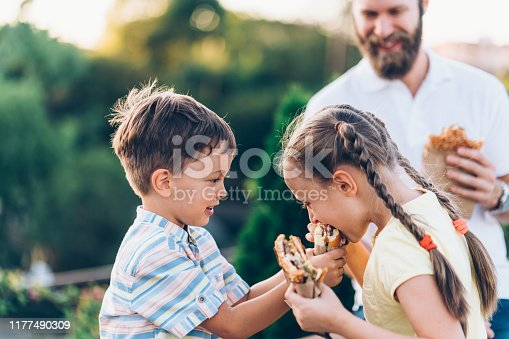Single father with kids eating fast food outside