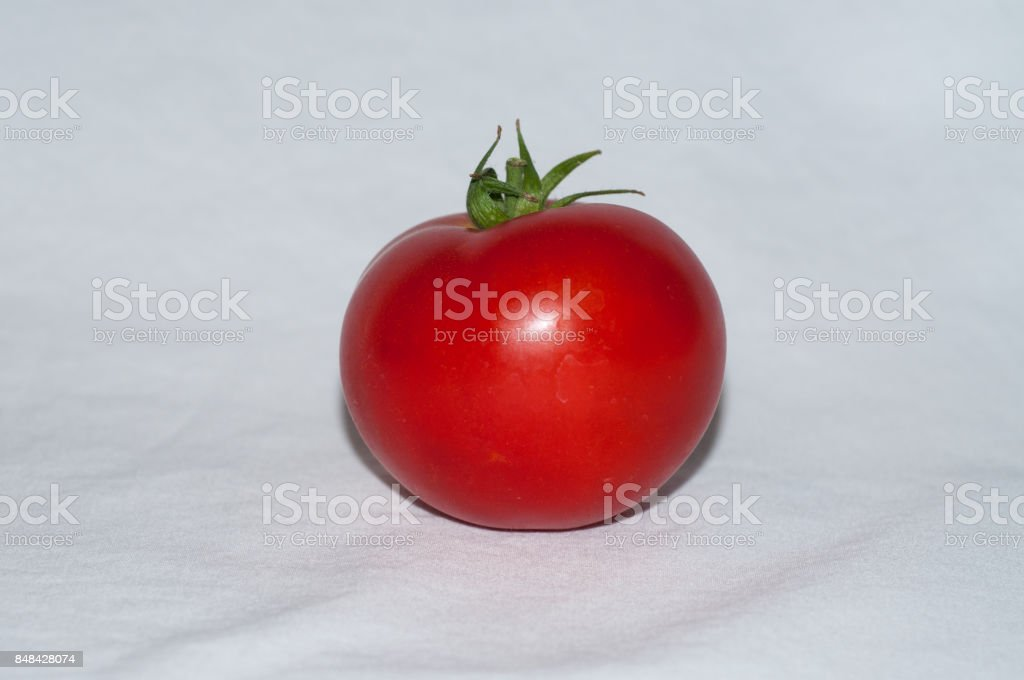 Single perfect red round tomato on white background. stock photo
