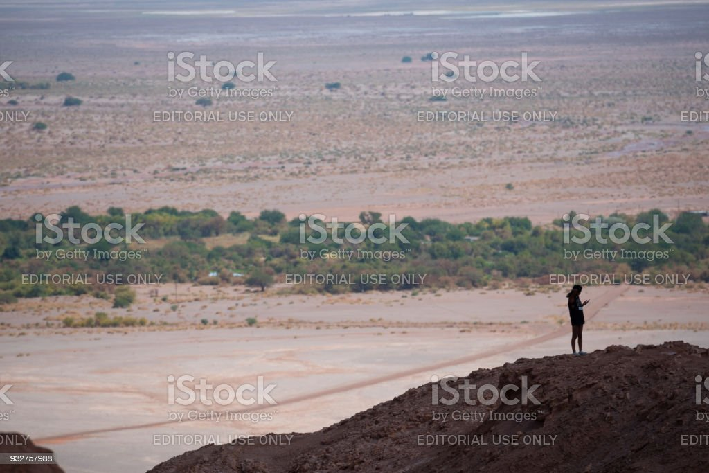 Single person on mountaintop. Using phone. Moon Valley in background. stock photo