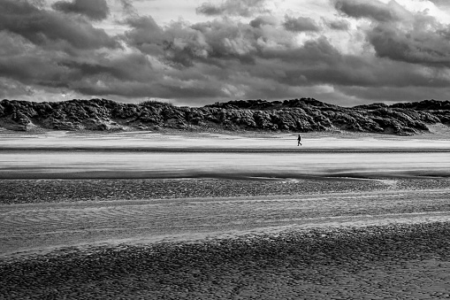 Single person walking alone at a windy beach at Bray-Dunes in France