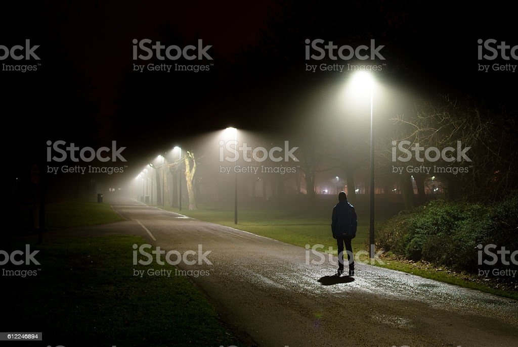 Single Person Walking on Street in the Dark Night Single Person Walking on Street in the Dark Night Adult Stock Photo