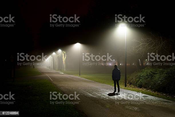 Single Person Walking On Street In The Dark Night Stock Photo - Download Image Now