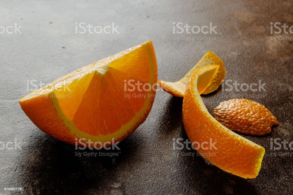 Single pieces of orange with orange peel on black table close up...