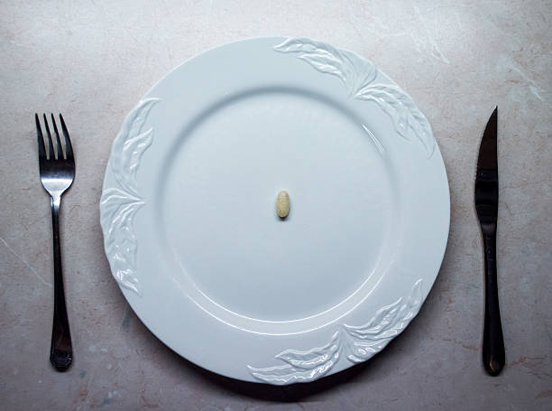 Single Pill/Tablet on a White Dinner Plate Overhead View stock photo