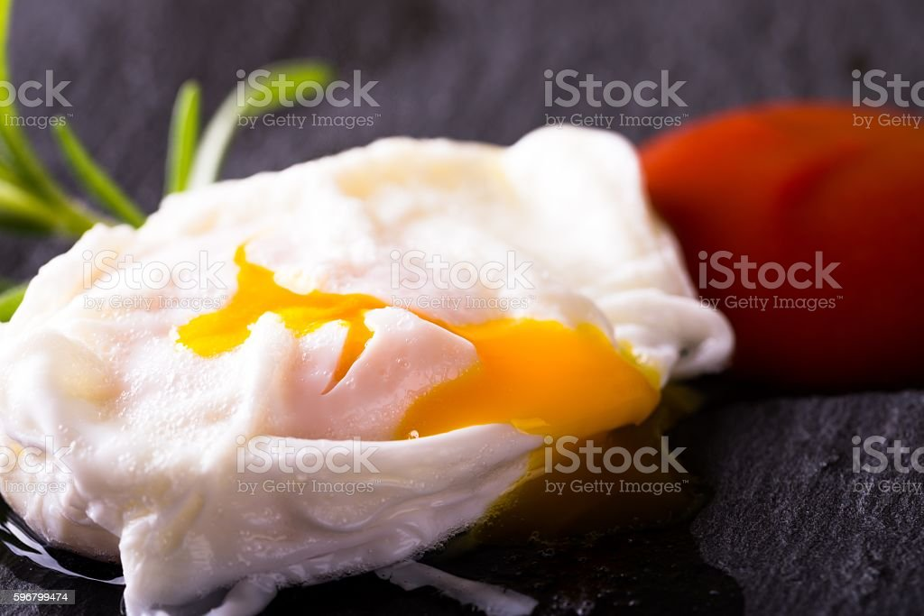 Single poached egg on slate stone with ketchup stock photo