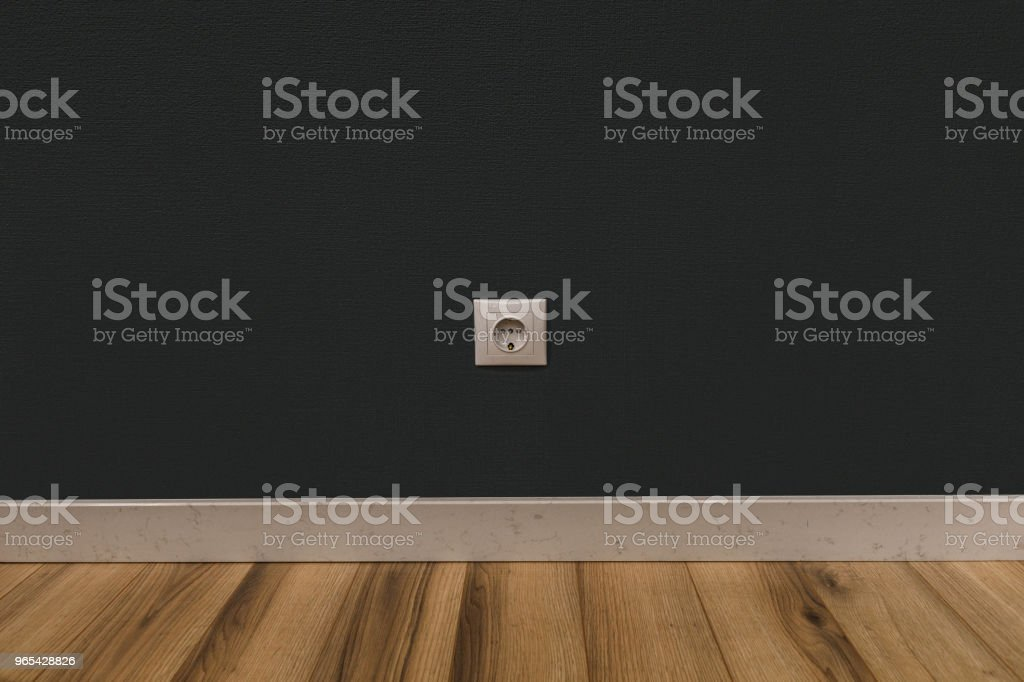 Single power socket in dark wall over wooden floor zbiór zdjęć royalty-free