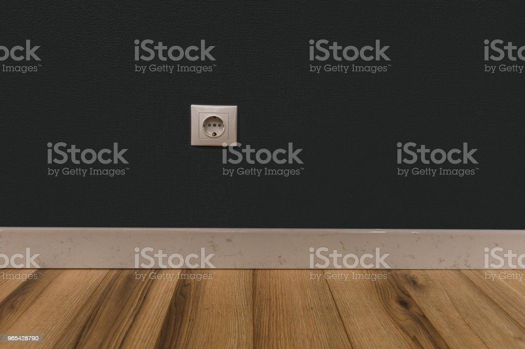 Prise de courant simple dans un mur vide sur plancher en bois - Photo de Ameublement libre de droits