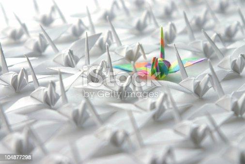 istock Single rainbow origami crane among many white cranes 104877298