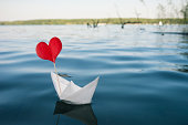 Single red heart on paper boat, natural water background