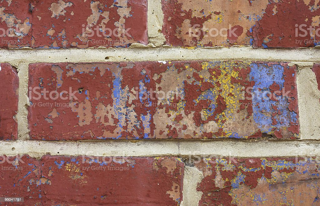 Blue yellow paint on red brick wall stock photo