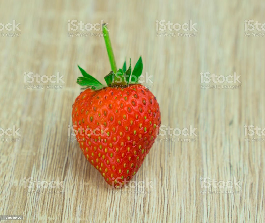 Single Red, Orange strawberry on the wooden background stock photo
