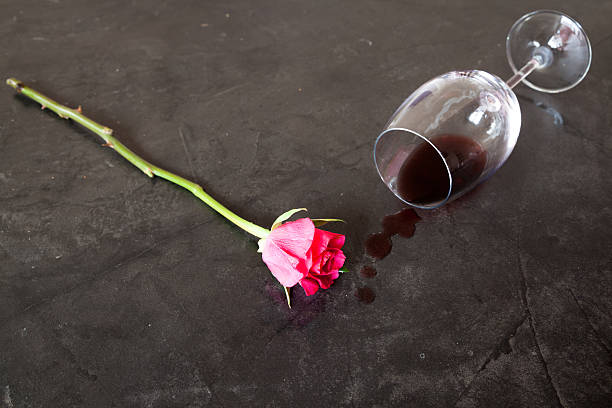 single red rose lies marblle surface beside spilled red wine stock photo
