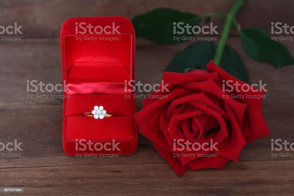 Single red roses and Diamond wedding ring in a red box on wooden background. stock photo