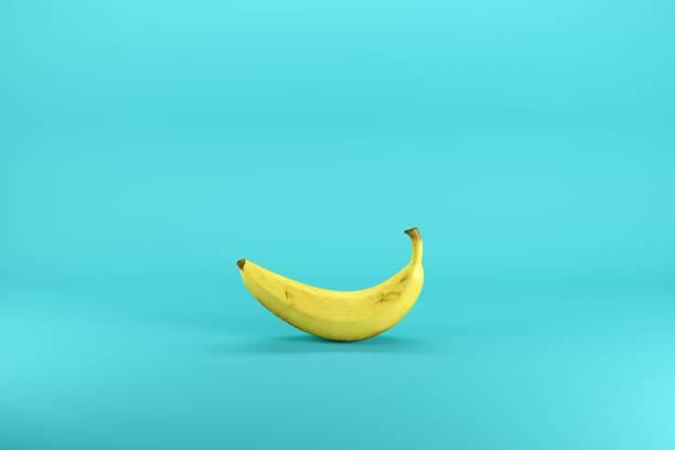 Einzelne, gelbe Banane, die auf blauem Hintergrund isoliert ist. Minimales Fruchtgedankkonzept. – Foto